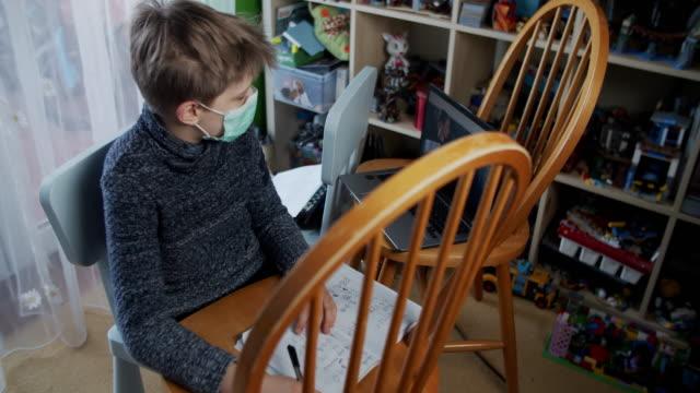 vídeos y material grabado en eventos de stock de niño que asiste a la clase de la escuela en línea desde su habitación. - orden de permanecer en casa
