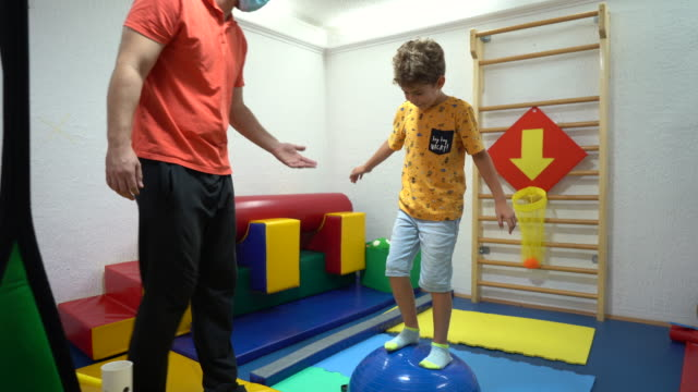little boy balancing on bosu ball at rehabilitation center - invisible disability stock videos & royalty-free footage