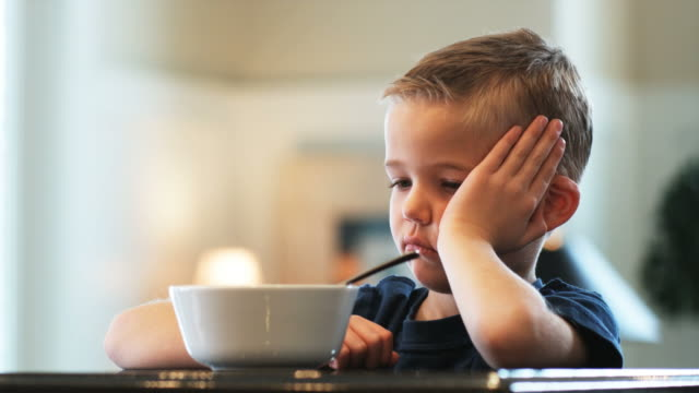 little boy being given a bowl of cereal that he does not want to eat
