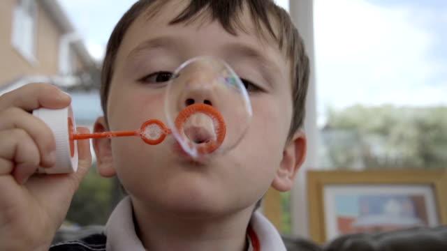 Little Boy Blowing Bubbles In slow Motion