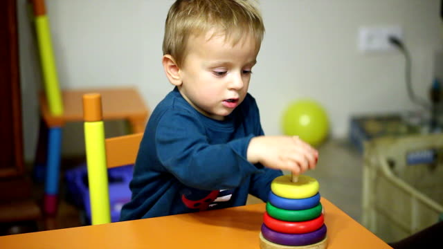 Little boy building a tower of wooden blocks