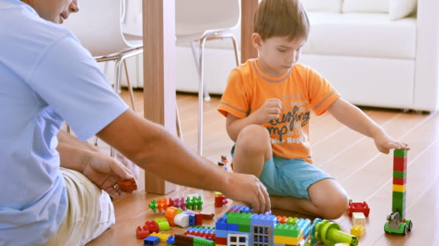 vídeos de stock, filmes e b-roll de garotinho, construção com tijolos de plástico junto com o pai dele - brinquedo