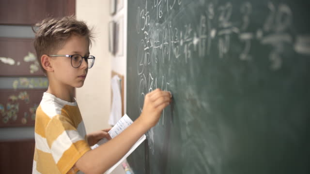 little boy calculating fractions on math lesson - blackboard visual aid stock videos & royalty-free footage