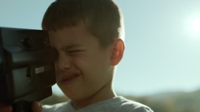 little boy capturing the moment with his camera - scoperta video stock e b–roll