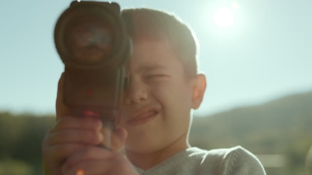 little boy capturing the moment with his camera - mirare video stock e b–roll