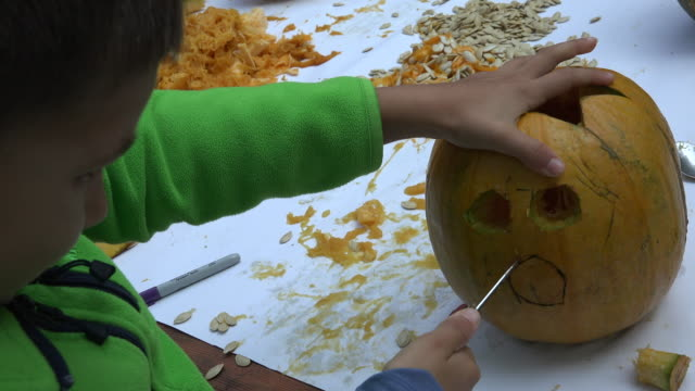 little boy carving a pumpkin by himself - carving knife stock videos and b-roll footage