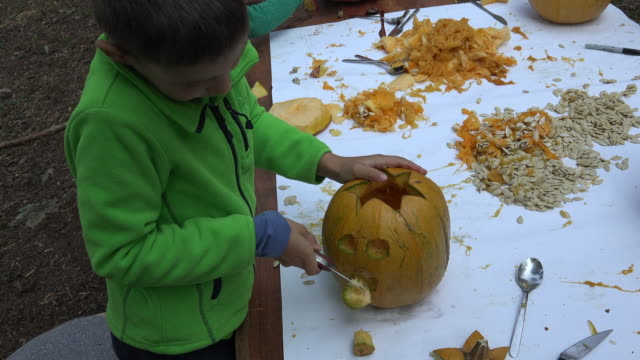 little boy carving the mouth of the pumpkin outside on the table - home decor stock videos & royalty-free footage