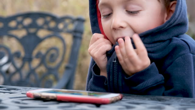little boy child looking at his smart phone - hooded top stock videos & royalty-free footage
