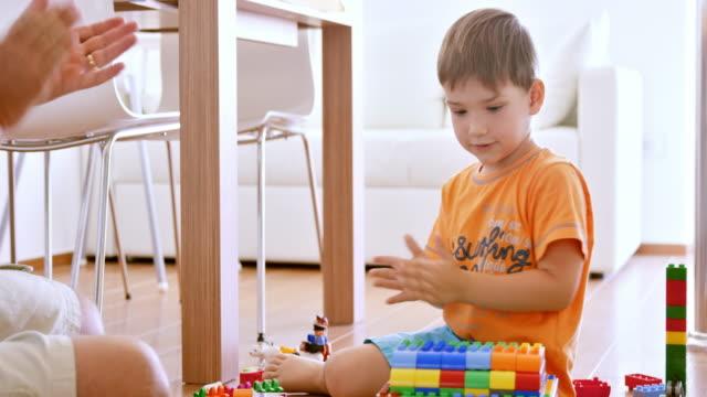vídeos de stock, filmes e b-roll de menino batendo palmas de mãos quando terminar a casa de tijolos de plástico - bloco de construção