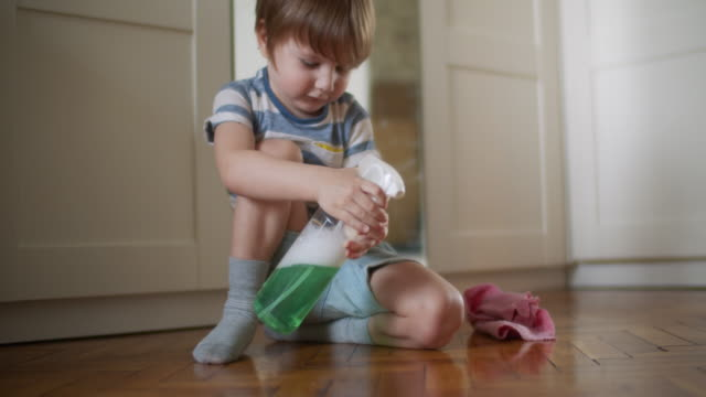 little boy cleaning parquet floor during housekeeping - spray cleaner stock videos & royalty-free footage