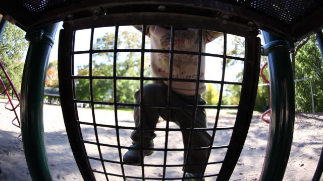 ms little boy climbing on outdoor jungle gym / toronto, ontario, canada - ジャングルジム点の映像素材/bロール
