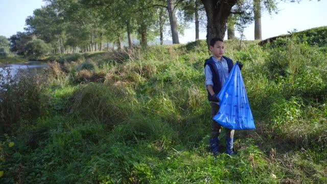 川のそばでプラスチックを集める小さな男の子 - ゴミ袋点の映像素材/bロール