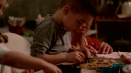 Little boy concentrating while cutting out shapes in a cookie dough