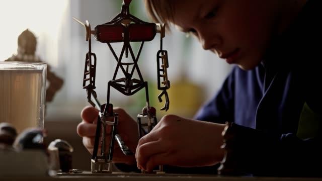 vídeos y material grabado en eventos de stock de pequeño niño construyendo un esqueleto de robot. - pieza de máquina