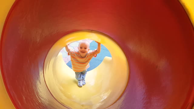 Little boy dangerously stuck on a slide at the playground