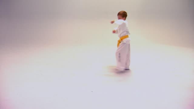 vidéos et rushes de little boy demonstrating tae kwon do moves - karaté