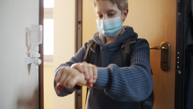 little boy disinfecting hands after returning from school - educazione video stock e b–roll