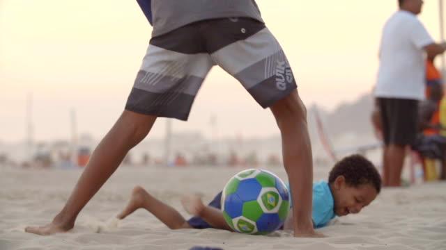 vídeos de stock, filmes e b-roll de little boy dives for brazilian soccer ball and kicks up sand on copacabana beach - irmão