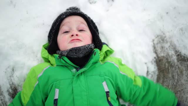 little boy doing a snow angel on few snow - hochgefühl stock-videos und b-roll-filmmaterial