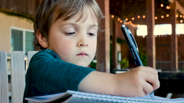 little boy doing his homework sitting at his home backyard - preschool student stock videos & royalty-free footage