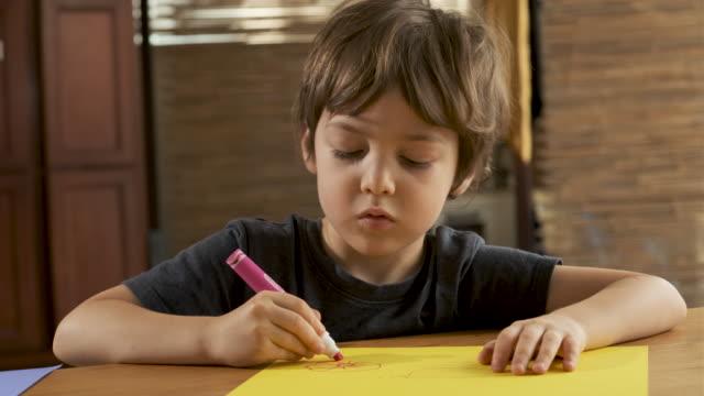 vídeos de stock e filmes b-roll de little boy doing his homework sitting at his home playroom - 4 5 anos