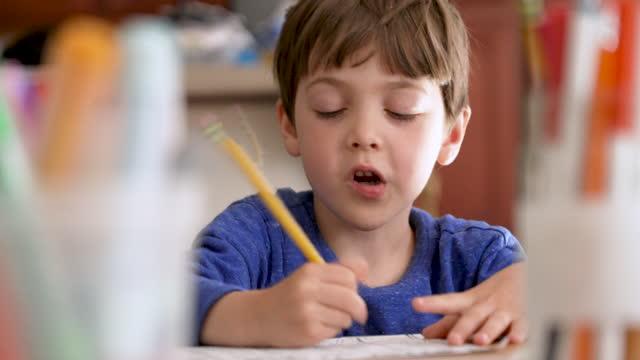 vídeos de stock e filmes b-roll de little boy doing his homework - 4 5 anos