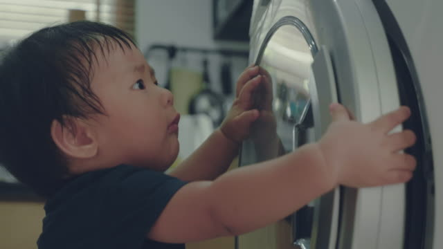 A little boy doing laundry at home