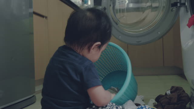 a little boy doing laundry at home - laundry stock videos and b-roll footage