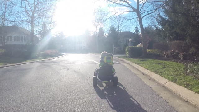 Little boy dressed in winter coat drives by in Go Cart then races off down a residential road with speed bump.