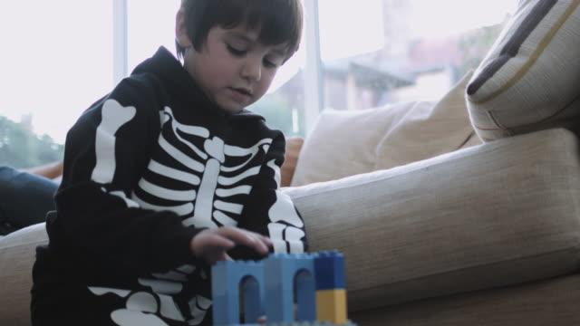 stockvideo's en b-roll-footage met little boy dressed up for halloween playing with building blocks - alleen jongens