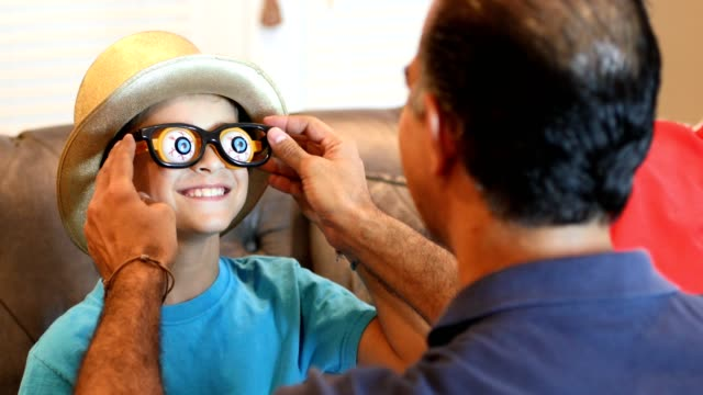 little boy dresses up for halloween with dad's help. - pair stock videos and b-roll footage