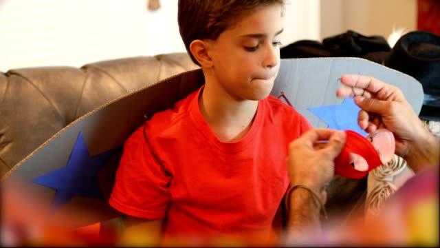 vídeos de stock e filmes b-roll de little boy dresses up for halloween with dad's help. - vestir se
