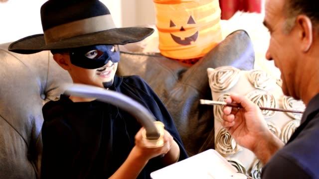 Jongetje aankleedt voor Halloween met papa's help.