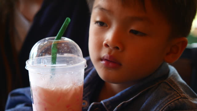 little boy drinking juice through a straw - cold drink stock videos and b-roll footage