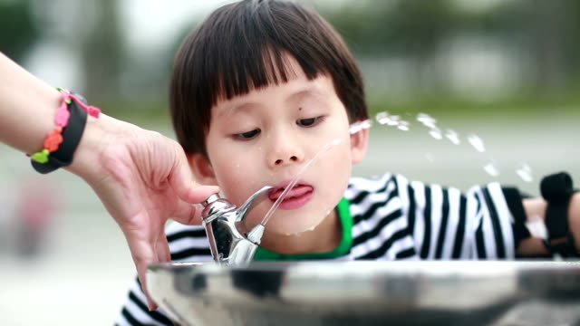 Little boy drinking tap water