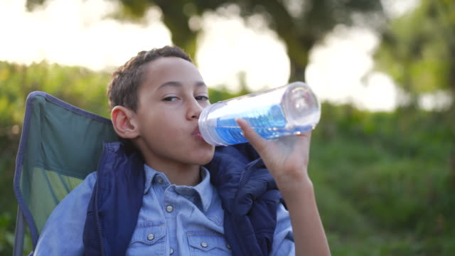 little boy drinking water from reusable water bottle while camping in nature - bottle stock videos & royalty-free footage