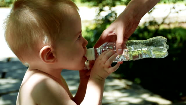 Little boy drinking water from special baby bottle