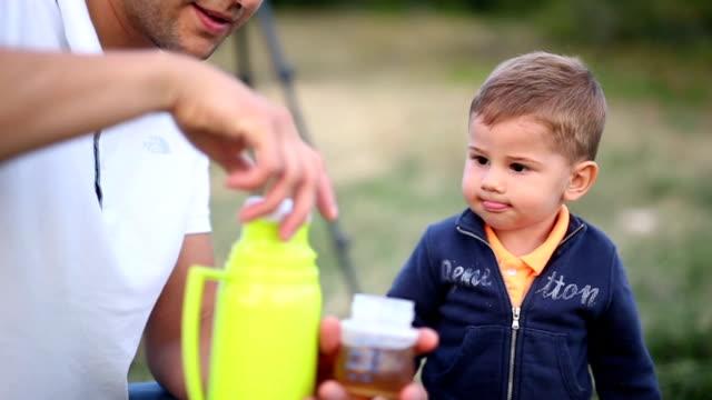 Little boy drinks water from a baby bottle