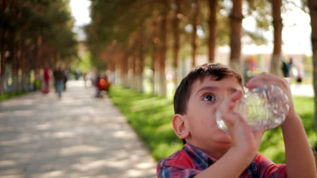 little boy drinks water from plastic bottle in the park. - plastic cap stock videos & royalty-free footage
