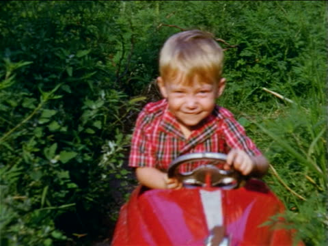 stockvideo's en b-roll-footage met 1955 home movie little boy driving red toy car toward camera + waving to camera / staten island - 1955
