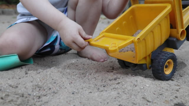little boy dumping out sand from dump truck - toy stock videos & royalty-free footage