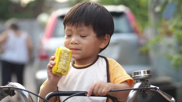 小さな男の子はトウモロコシを食べる - 野菜 とうもろこし点の映像素材/bロール