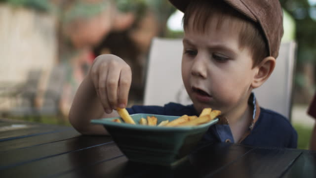 little boy eating french fries in a cafe in summer - boys stock videos & royalty-free footage
