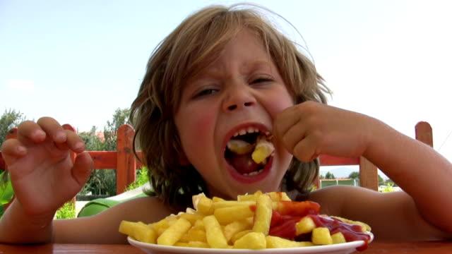 vidéos et rushes de petit garçon manger des frites - pomme de terre