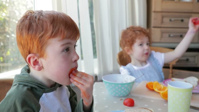 vídeos de stock e filmes b-roll de little boy eating his orange - laranja