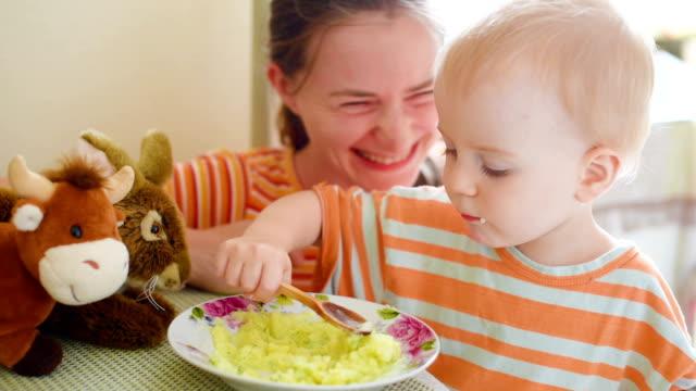 Little boy eating mashed potatoes