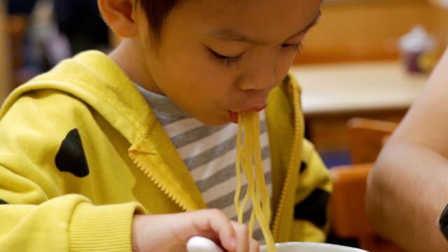 vídeos y material grabado en eventos de stock de un niño comiendo fideos en el restaurante japonés. - 2 3 años