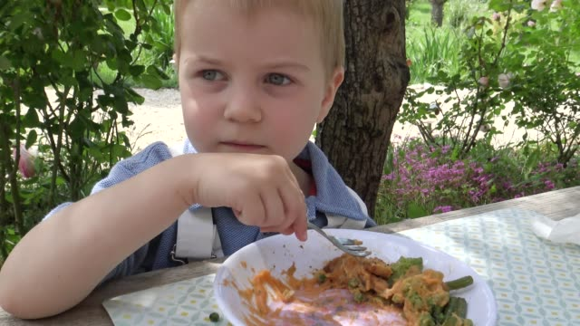 Little boy eating outdoors