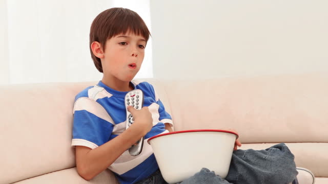 vídeos de stock e filmes b-roll de boy eating popcorn while he watches television - controlo remoto