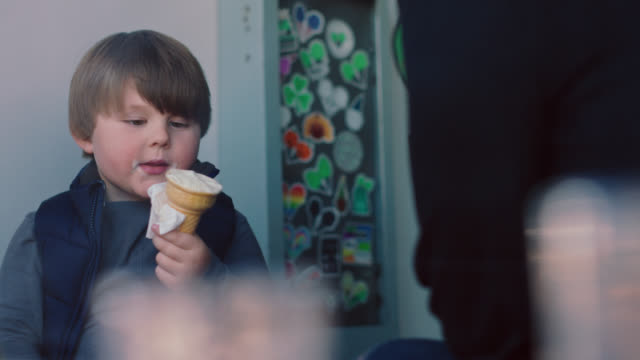 vidéos et rushes de a little boy eats an ice cream cone next to the window of an ice cream parlor with his mother - lécher